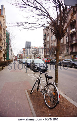 Poznan, Poland - March 8, 2019: Bicycle locked on a metal barrier next to tree on a sidewalk in the Slowackiego street in the city center. - Stock Photo