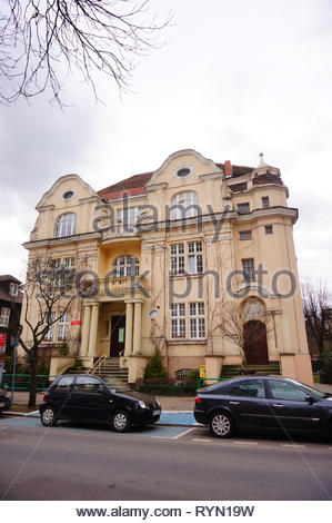 Poznan, Poland - March 8, 2019: Parked cars in frond of a kindergarten building on the Slowackiego street in the city center. - Stock Photo