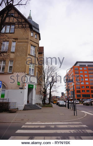 Poznan, Poland - March 8, 2019: Zebra crossing leading to a small Zabka grocery store in a old building on the Slowackiego street. - Stock Photo