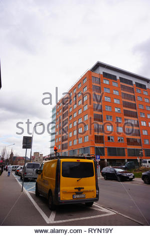 Poznan, Poland - March 8, 2019: Yellow technical service bus wrongly parked close by the Globis office building in the city center. - Stock Photo