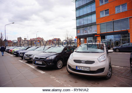 Poznan, Poland - March 8, 2019: Row of parked cars on parking spots close by the Globis office building with Orange telecommunication shop on the Slow - Stock Photo