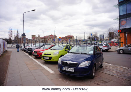 Poznan, Poland - March 8, 2019: Row of parked cars on parking spots on the Slowackiego street in the city center. - Stock Photo