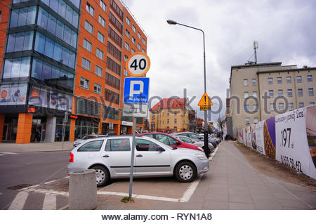 Poznan, Poland - March 8, 2019: Row of parked cars on paid parking spots close by office building on the Slowackiego street in the city center on a cl - Stock Photo