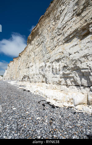 White chalk rock wall at Birling Gap, Sussex, with clear sediment layers and pebble beach beneath, sunny and blue sky, wide angle - Stock Photo