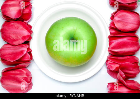 Green Apple lies on a white plate with white background next to multi-colored tulips. closeup - Stock Photo
