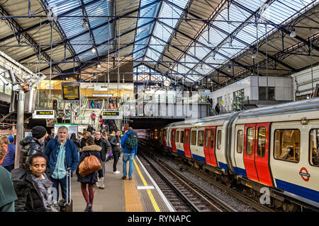 Passengers waiting for a train at  Earls Court Underground Station in SW London - Stock Photo