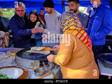 Local woman with head scarf preparing turkish pancakes (gozleme) for customers at a fair in Antalya, Turkey - December 29, 2018 - Stock Photo