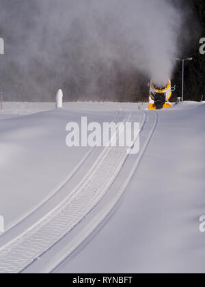 Snowmobile tracks in pristine snow leading towards a snow cannon - Stock Photo