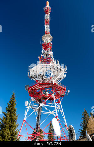 Steel transmission tower of cellular telecommunications network in white and red color on the background of blue sky. - Stock Photo