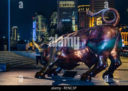 SHANGHAI, CHINA, DECEMBER - 2018 - Urban night scene depicting the famous bull sculpture at bund zone in shanghai city, china - Stock Photo