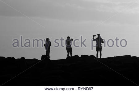 A black and white image of three young people - two male, one female - using smartphones in various ways; standing on rocks, silhouetted against sky. - Stock Photo