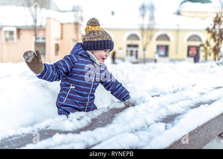 A little boy of 3-6 years old plays in the winter in the city, happy having fun playing snowballs, collecting snow from the bench, emotions of joy and