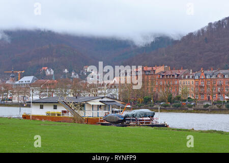 Boat anchored at the Neckar river meadow near city center of Heidelberg, with old buildings and beautiful hill landscape with mist raising in Germany - Stock Photo