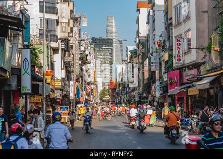 Ho Chi Minh, Vietnam - January 7, 2019: Bui Vien Street crowded with people and road traffic, its numerous signboards & Bitexco Financial Tower. - Stock Photo