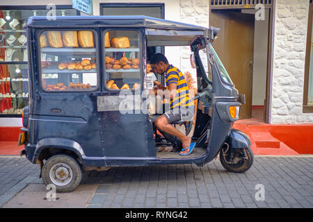 Bread delivery man in black tuktuk in the old part of Galle, under the look of  kid buying . Galle, Sri Lanka, January 9 2018 - Stock Photo