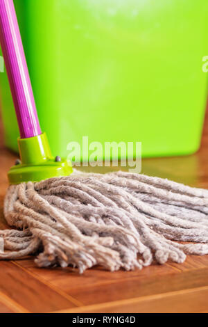 Rope mop for cleaning the floor on the background of a plastic bucket - Stock Photo