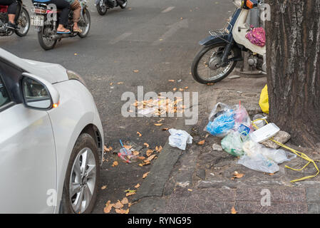 Ho Chi Minh City, Vietnam - January 8, 2019: a heap of garbage on the sidewalk under a tree in the center of the city with street traffic seen. - Stock Photo