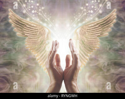 Sensing Angelic Energy - Male hands reaching up into a beautiful pair of golden Angel wings with white light and sparkles flowing  between - Stock Photo