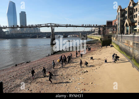 A view of schoolchildren school group mudlarking on the north sandy beach side of the River Thames in winter sunshine London England UK  KATHY DEWITT - Stock Photo