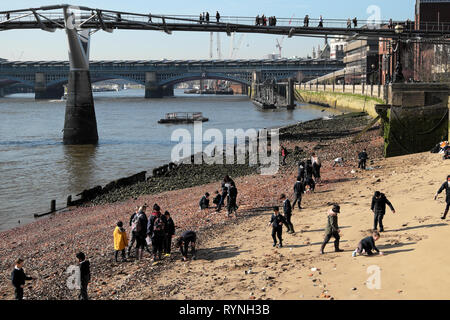 A view of schoolchildren in uniform school group mud larking on the north sandy shore of the River Thames in winter London England UK  KATHY DEWITT - Stock Photo