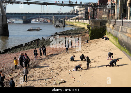 A view of schoolchildren school group mudlarking and playing in sand beach by the Millennium Bridge and River Thames in London England UK KATHY DEWITT - Stock Photo