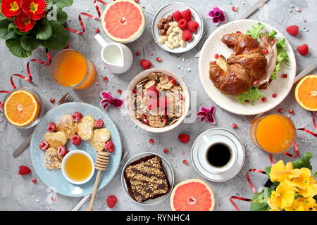 Breakfast food table. Festive brunch set, meal variety with pancakes, croissant, juice, granola and fresh fruits. Top view with copy space. - Stock Photo