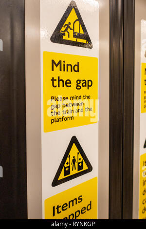 Mind The Gap danger warning sign on the interior of a closed London Tube carriage Door - Stock Photo