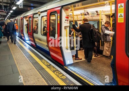 Commuters boarding a London Tube train at a quiet travel time, man standing in the carriage before doors close - Stock Photo