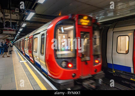 London Tube train leaves the platform at a quiet travel time, after the doors close - Stock Photo