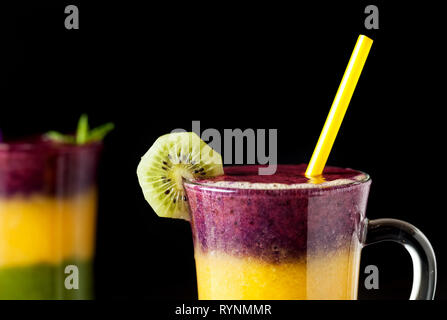 Two glass of smoothie with colorful layers from kiwi, oranges and blackberry on black background close up - Stock Photo
