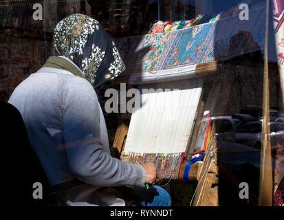 hand weaving carpet.Turkush Lady weaving carpet handmade carpet - Stock Photo