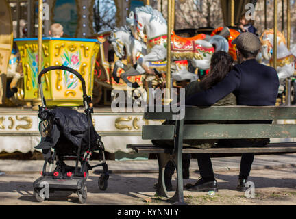 Couple near the carousel sitting on the bench waiting for a child rides carousel. - Stock Photo