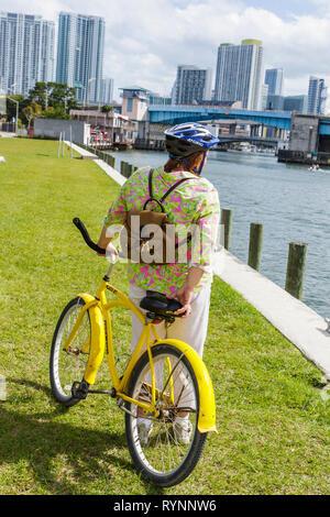 Miami Florida River Bike Miami Days community event woman cyclist bicycle yellow helmet safety downtown skyline river brid - Stock Photo