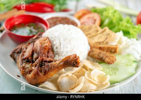 Nasi lemak kukus with fried drumstick, popular traditional Malaysian local food. - Stock Photo