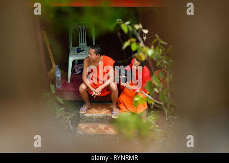 Two Buddhist Monks, framed by a wall with arches are talking each others in Luang Prabang, Laos. - Stock Photo