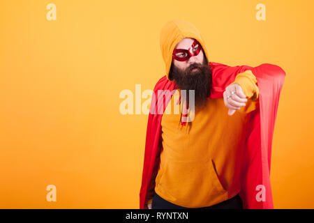Hipster with long beard dressed in superhero costume looking away over yellow background. Yellow hoodie. red mask. Brave man. - Stock Photo