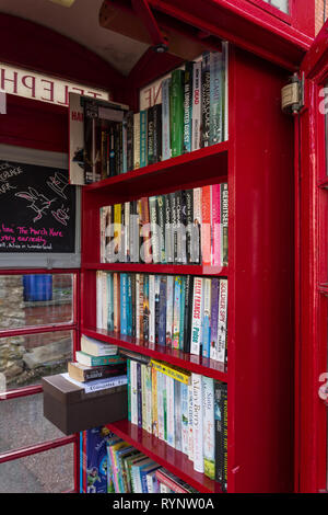 Old red telephone kiosk converted to use as a book exchange in the village of Collingtree, Northamptonshire, UK - Stock Photo