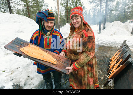 Saariselka, Finland - april 24, 2013: Local saami couple holding wooden board with a smoked salmon fillet prepared on open air fire in Saariselka, Fin - Stock Photo