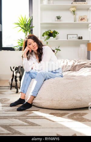 Pretty young woman relaxing on a bean bag near a window in a small apartment. - Stock Photo