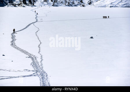A man walking a road in the snow in the mountains. Winter mountain landscape. - Stock Photo