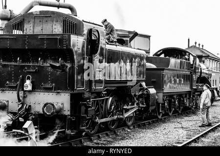 Black & white, nostalgic photograph of two vintage UK steam locomotives with crew, stationary on railway track at SVR vintage steam railway station. - Stock Photo