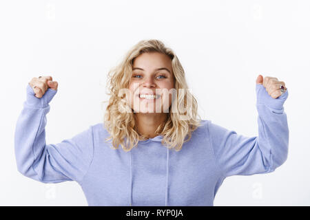 Who is champion. Portrait of active and enthusiastic happy good-looking young girlfriend with short haircut and blue eyes in purple hoodie raising - Stock Photo