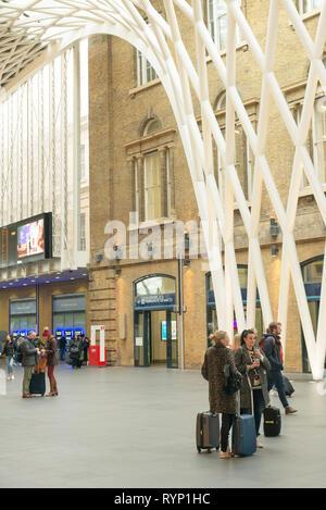 Passengers wait for a train in Kings Cross railway station, London, UK - Stock Photo