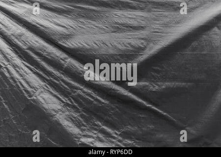 Full frame background of a wrinkled tarp texture in black and white. - Stock Photo