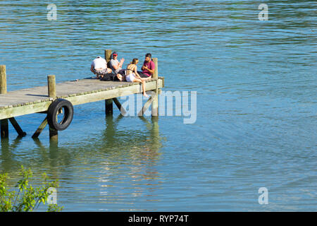 CROMWELL NEW ZEALAND - OCTOBER 21 2019; Lake Dunstan scene with young group young people sitting together on end of jetty Cromwell New Zealand - Stock Photo