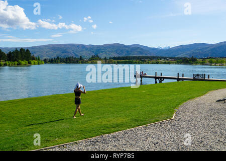 CROMWELL NEW ZEALAND - OCTOBER 21 2019; Lake Dunstan scene with young woman wlking along lake edge and group young people sitting together on end of j - Stock Photo