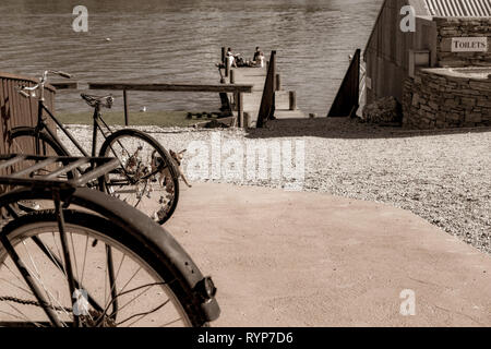 CROMWELL, NEW ZEALAND - OCTOBER 21 2019; Old bicyle wheels in street in small town with group four youth in distance on jetty on Lake Dunstan aged ima - Stock Photo