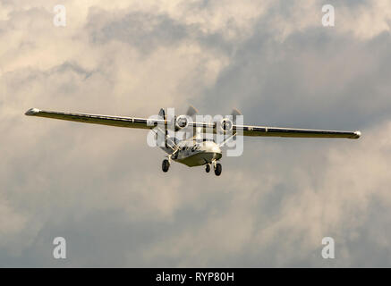 A USAF Catalina spotter plane flying over Duxford - Stock Photo