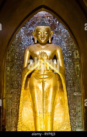 Gold buddha statue inside Ananda pagoda at Bagan in Myanmar - Stock Photo