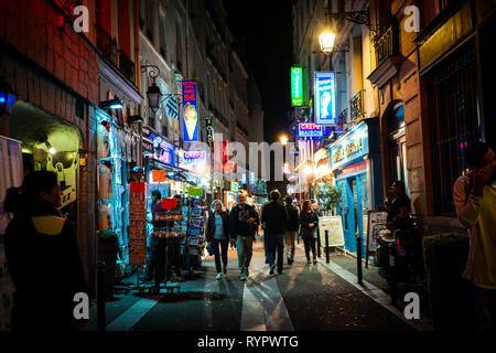 Tourists pass shops and cafes as they walk the colorful neon streets late at night in the Latin Quarter section of Paris France - Stock Photo